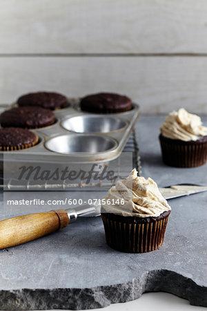 Frosting freshly made cupcakes, studio shot