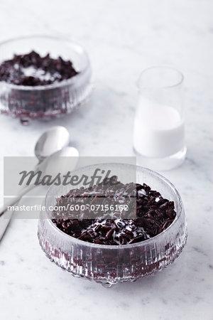 Black Rice Pudding in bowl with coconut milk, studio shot