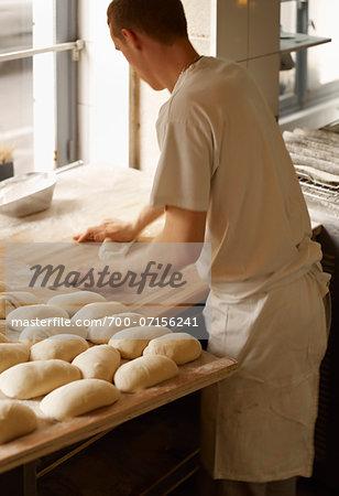 Male baker shaping baguette bread dough by hand in bakery, Le Boulanger des Invalides, Paris, France