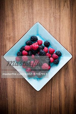 Studio shot of blackberries and raspberries in bowl