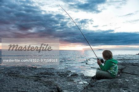 Boy fishing in sea at dusk