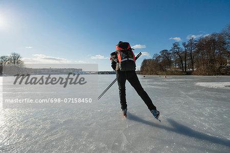Rear view of man skating on frozen lake