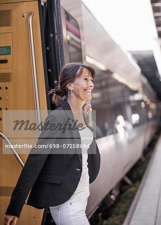 Happy businesswoman disembarking train