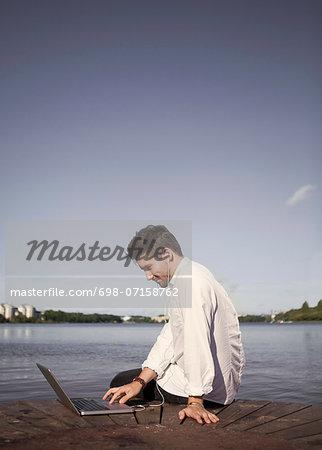 Businessman listening to music while using laptop on boardwalk at seaside
