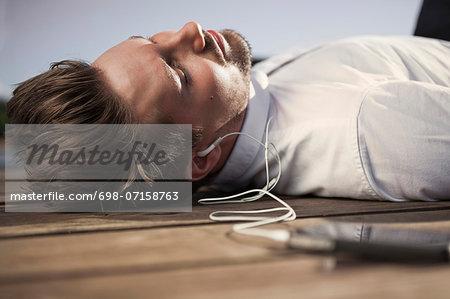 Businessman listening music through mobile phone while lying on boardwalk