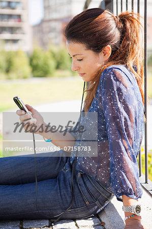 Businesswoman listening music through mobile phone outdoors