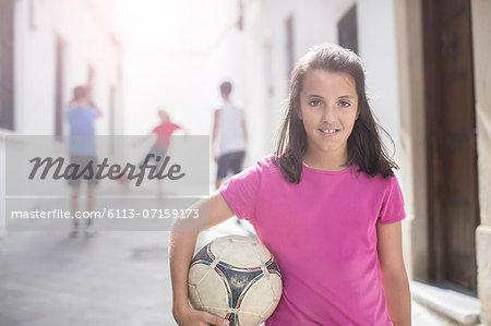 Girl holding soccer ball in alley
