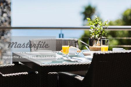 Breakfast on luxury patio dining table overlooking ocean