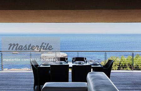 Dining table on luxury balcony overlooking ocean