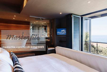 Modern master bedroom and bathroom overlooking ocean