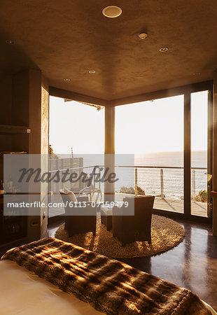 Luxury bedroom overlooking ocean at sunset