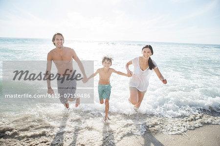 Family running in surf on beach