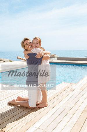 Grandmother hugging granddaughter at poolside