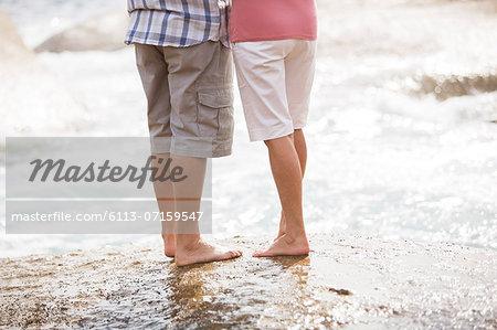 Senior couple standing on rock at beach
