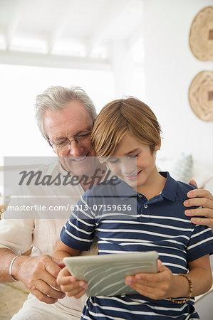 Older man and grandson using digital tablet