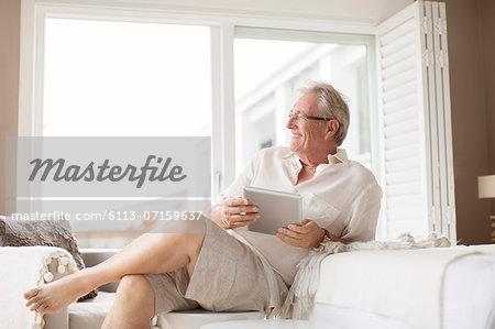 Older man using digital tablet in bedroom