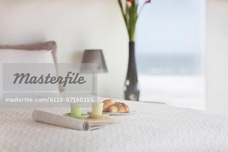Breakfast on bed in modern bedroom