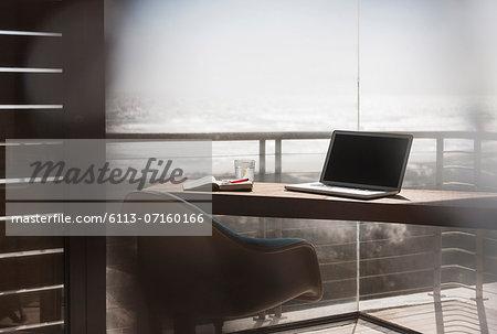 Laptop on desk in modern home office overlooking ocean