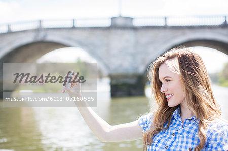 Woman taking self-portrait along river