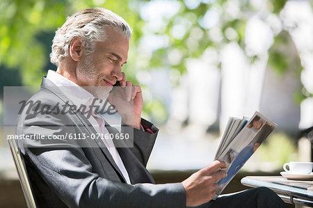 Businessman reading magazine at sidewalk cafe
