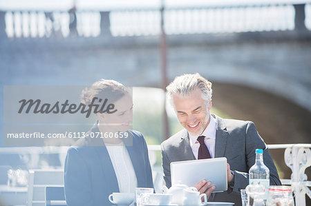 Business people talking at sidewalk cafe