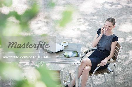 Businesswoman sitting at sidewalk cafe