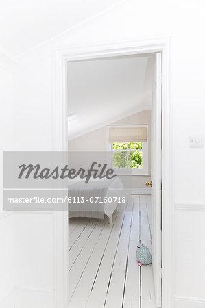 Doorway to whitewashed bedroom