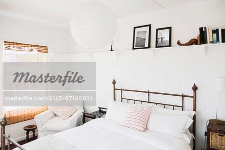 Shelf above bed in white bedroom