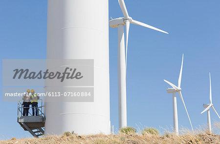 Workers talking on wind turbine in rural landscape