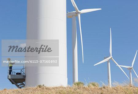 Worker examining wind turbine in rural landscape
