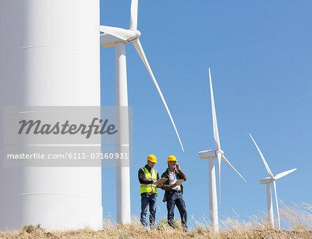 Workers talking by wind turbines in rural landscape