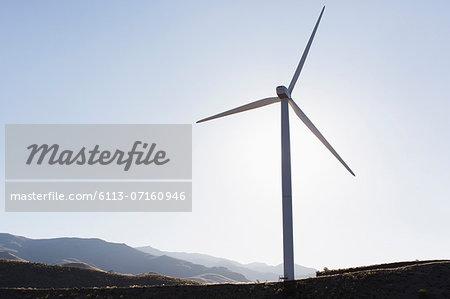 Silhouette of wind turbine in rural landscape