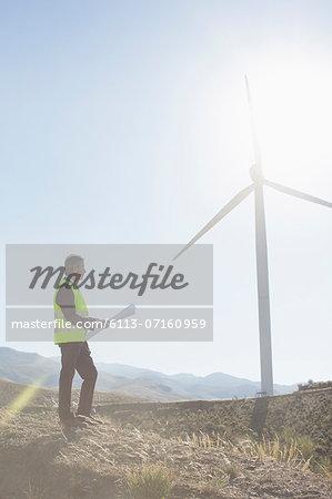 Businessman examining wind turbine in rural landscape