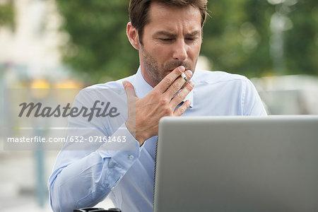 Businessman smoking while using laptop computer outdoors