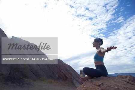 Woman sitting cross legged at Vazquez Rocks, meditating