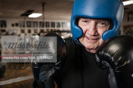 Senior man wearing boxing gloves and helmet