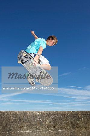 Teenage boy mid air on skateboard