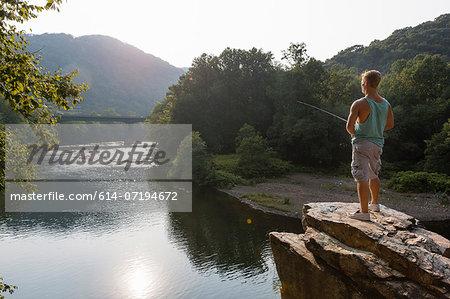 Young man fishing from rock ledge, Hamburg, Pennsylvania, USA
