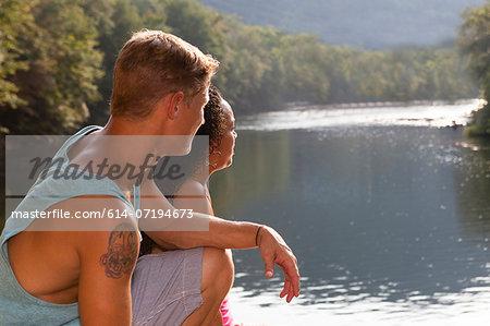 Young couple sitting by river, Hamburg, Pennsylvania, USA