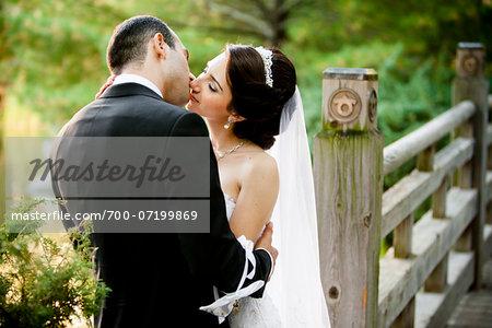 Bride and groom kissing outdoors in public garden, in Autumn, Ontario, Canada