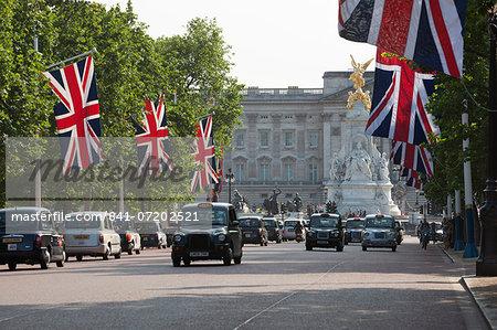 Buckingham Palace with taxis and Union Jacks along The Mall, London, England, United Kingdom, Europe
