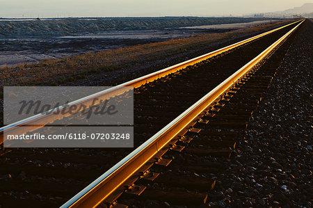 Railroad tracks extending across the flat Utah desert landscape, at dusk.