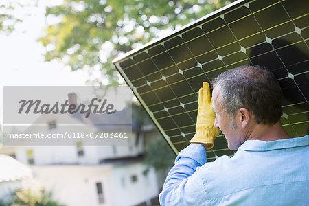 A man carrying a solar panel towards a building under construction.