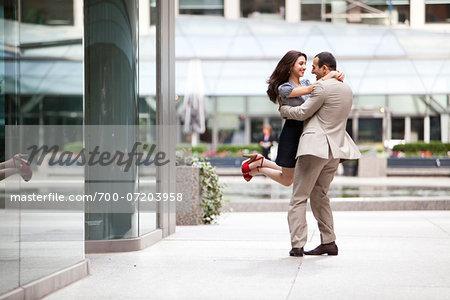 Excited couple embracing on ciity street sidewalk, Toronto, Ontario, Canada