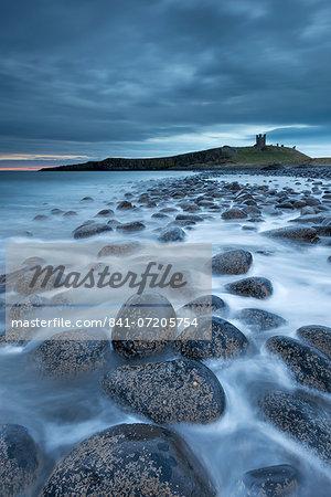 Dunstanburgh Castle at dawn from Embleton Bay, Northumberland, England, United Kingdom, Europe