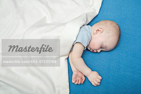 Sleeping baby on bed under blanket