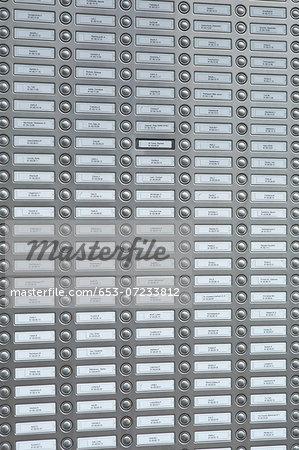 Rows of doorbells on a metal panel