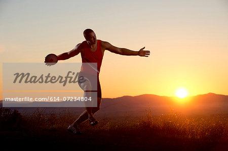 Young man preparing to throwing discus at sunset