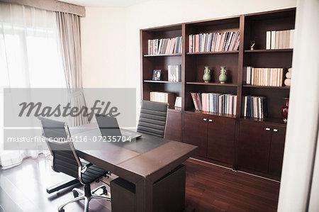 Modern home office with bookshelves.
