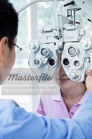 Optometrist doing an eye exam on young woman